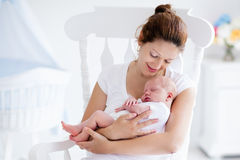 Νέα μητέρα και νεογέννητο μωρό στην άσπρη κρεβατοκάμαρα Στοκ φωτογραφίες με δικαίωμα ελεύθερης χρήσης