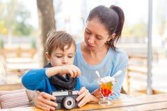 Νέα μητέρα και ο γιος της σε έναν καφέ Η έννοια της οικογένειας στοκ εικόνα
