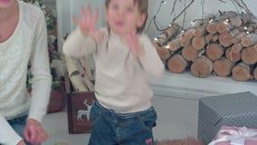 Νέα μητέρα και συγκινημένα μετρώντας χριστουγεννιάτικα δώρα αγοριών στα δάχτυλά του απόθεμα βίντεο