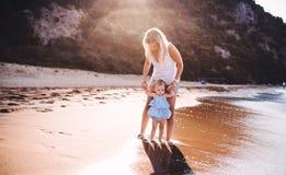 Νέα μητέρα με ένα κορίτσι μικρών παιδιών στην παραλία στις καλοκαιρινές διακοπές στο ηλιοβασίλεμα στοκ εικόνα