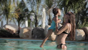 Νέα μητέρα με λίγο χαριτωμένο κορίτσι που έχει τη διασκέδαση στην πισίνα τη θερινή ημέρα απόθεμα βίντεο