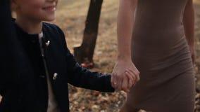 Νέα μητέρα με μια μικρή κόρη που περπατά στο πάρκο φθινοπώρου οικογένεια έννοιας ευτ& φιλμ μικρού μήκους