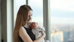 Νέα μητέρα με μια νεογέννητη κόρη που στέκεται κοντά στο παράθυρο απόθεμα βίντεο