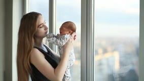 Νέα μητέρα με μια νεογέννητη κόρη που στέκεται κοντά στο παράθυρο φιλμ μικρού μήκους