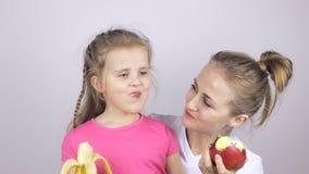 Νέα μητέρα με την κόρη της που χαμογελά και που τρώει την μπανάνα και το μήλο φιλμ μικρού μήκους