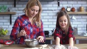 Νέα μητέρα με την ξανθή μακρυμάλλη μίξη στο πιάτο και μικρό χαριτωμένο άτακτο παιχνίδι κοριτσιών με το αλεύρι στον πίνακα κουζινώ απόθεμα βίντεο
