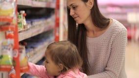 Νέα μητέρα με τις αγορές κορών μωρών στην υπεραγορά απόθεμα βίντεο