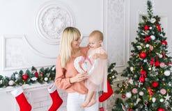 Νέα μητέρα με το κοριτσάκι μπροστά από το χριστουγεννιάτικο δέντρο Στοκ Εικόνα