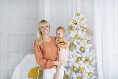 Νέα μητέρα με το κοριτσάκι μπροστά από το χριστουγεννιάτικο δέντρο στοκ φωτογραφία με δικαίωμα ελεύθερης χρήσης