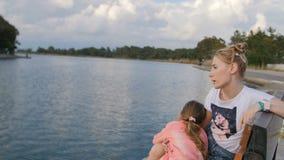 Νέα μητέρα με το μικρό κορίτσι που απολαμβάνει το ηλιόλουστο βράδυ στο πάρκο κοντά στη λίμνη συνεδρίαση πάγκων απόθεμα βίντεο