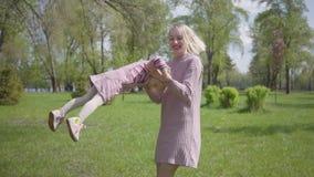 Νέα μητέρα πορτρέτου αρκετά που περιστρέφει την κόρη σε ετοιμότητα στη φύση την ημέρα άνοιξη Παιχνίδι γυναικών και παιδιών στο πά απόθεμα βίντεο