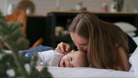 Νέα μητέρα που αγκαλιάζει το νεογέννητο παιδί της Νοσηλευτικό μωρό Mom Γυναίκα και νέος - το γεννημένο αγόρι χαλαρώνει σε μια άσπ απόθεμα βίντεο