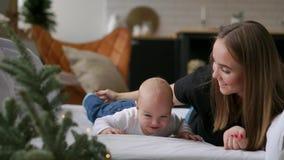 Νέα μητέρα που αγκαλιάζει το νεογέννητο παιδί της Νοσηλευτικό μωρό Mom Γυναίκα και νέος - το γεννημένο αγόρι χαλαρώνει σε μια άσπ φιλμ μικρού μήκους