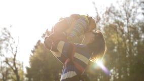 Νέα μητέρα που ανυψώνει το μωρό της στον αέρα που δίνει του ένα φιλί Στοκ Εικόνα