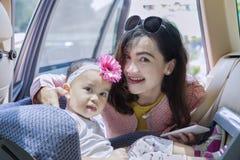 Νέα μητέρα που βάζει το παιδί της στο κάθισμα Στοκ φωτογραφία με δικαίωμα ελεύθερης χρήσης