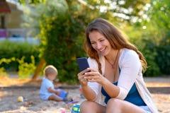 Νέα μητέρα που γελά σε ένα μήνυμα κειμένου στοκ εικόνα με δικαίωμα ελεύθερης χρήσης