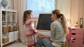 Νέα μητέρα που εξηγεί την αριθμητική σε χαριτωμένο λίγη κόρη στο σπίτι απόθεμα βίντεο