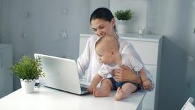 Νέα μητέρα που εργάζεται με το lap-top στο σπίτι απόθεμα βίντεο