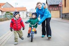 Νέα μητέρα που διδάσκει σε 2 της χρονών λίγο γιο για να οδηγήσει ένα ποδήλατο Στοκ φωτογραφίες με δικαίωμα ελεύθερης χρήσης