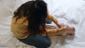 Νέα μητέρα που κάνει ενισχύοντας τις ασκήσεις για το μωρό παίζοντας γυναίκα παιδιών φιλμ μικρού μήκους