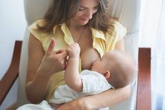 Νέα μητέρα που κρατά το αγοράκι της, που αυτός, που κάθεται μέσα Στοκ Εικόνες