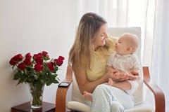 Νέα μητέρα που κρατά το αγοράκι της, που παίζει με τον, που κάθεται μέσα Στοκ Εικόνες