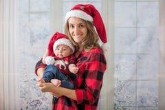 Νέα μητέρα, που κρατά το αγοράκι newborh της, νήπιο με το santa εκτάριο Στοκ φωτογραφία με δικαίωμα ελεύθερης χρήσης