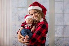 Νέα μητέρα, που κρατά το αγοράκι newborh της, νήπιο με το santa εκτάριο Στοκ φωτογραφίες με δικαίωμα ελεύθερης χρήσης