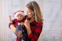 Νέα μητέρα, που κρατά το αγοράκι newborh της, νήπιο με το santa εκτάριο Στοκ εικόνες με δικαίωμα ελεύθερης χρήσης