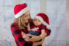 Νέα μητέρα, που κρατά το αγοράκι newborh της, νήπιο με το santa εκτάριο Στοκ Φωτογραφίες