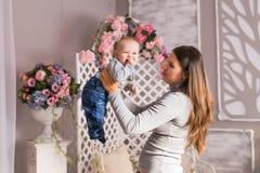 Νέα μητέρα που κρατά το νεογέννητο παιδί της Η γυναίκα και το αγοράκι χαλαρώνουν σε μια άσπρη κρεβατοκάμαρα Εσωτερικό βρεφικών στ Στοκ εικόνα με δικαίωμα ελεύθερης χρήσης