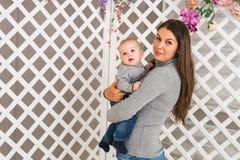 Νέα μητέρα που κρατά το νεογέννητο παιδί της Η γυναίκα και το αγοράκι χαλαρώνουν σε μια άσπρη κρεβατοκάμαρα Εσωτερικό βρεφικών στ Στοκ Εικόνες