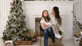 Νέα μητέρα που μιλά στο τηλέφωνο με την ελαφρώς τρυπημένη συνεδρίαση κορών στην περιτύλιξή της δίπλα στο χριστουγεννιάτικο δέντρο στοκ εικόνα με δικαίωμα ελεύθερης χρήσης