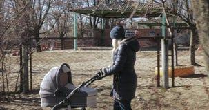 Νέα μητέρα που περπατά με έναν περιπατητή απόθεμα βίντεο