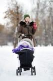 Νέα μητέρα που περπατά με το μωρό στον περιπατητή το χειμώνα Στοκ εικόνες με δικαίωμα ελεύθερης χρήσης