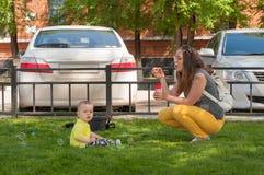 Νέα μητέρα που στηρίζεται με το γιο της στις φυσαλίδες θερινών πάρκων και χτυπήματος Στοκ φωτογραφία με δικαίωμα ελεύθερης χρήσης