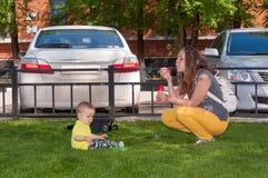 Νέα μητέρα που στηρίζεται με το γιο της στις φυσαλίδες θερινών πάρκων και χτυπήματος Στοκ Φωτογραφία