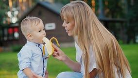 Νέα μητέρα που ταΐζει ένα παιδί με μια μπανάνα απόθεμα βίντεο