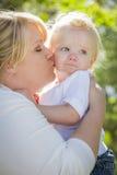 Νέα μητέρα που φιλά και που κρατά το λατρευτό αγοράκι της Στοκ Εικόνες