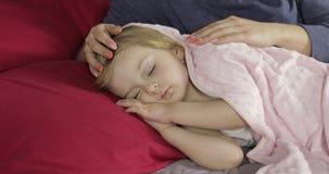 Νέα μητέρα που φροντίζει την λίγο κοριτσάκι ενώ κοιμάται Κορίτσι στο κρεβάτι απόθεμα βίντεο