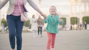 Νέα μητέρα που χαμογελά μαζί το τρέξιμο κορών στο ηλιόλουστο πάρκο οικογένεια έννοιας ευτ& απόθεμα βίντεο