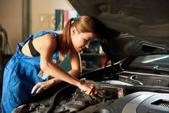 Νέα μηχανική γυναίκα αυτοκινήτων που επισκευάζει το αυτοκίνητο στο πρατήριο βενζίνης Στοκ εικόνα με δικαίωμα ελεύθερης χρήσης