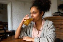 Νέα μικτή γυναίκα φυλών που πίνει το χυμό από πορτοκάλι Στοκ Εικόνες