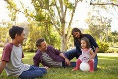 Νέα μικτή οικογενειακή χαλάρωση φυλών με τη σφαίρα ποδοσφαίρου σε ένα πάρκο στοκ φωτογραφία