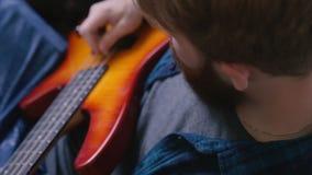 Νέα μοντέρνη γενειοφόρος βαθιά κιθάρα μελωδίας παιχνιδιού κιθάρων παιχνιδιού hipster απόθεμα βίντεο