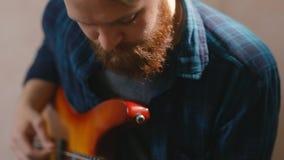Νέα μοντέρνη γενειοφόρος βαθιά κιθάρα μελωδίας παιχνιδιού κιθάρων παιχνιδιού hipster φιλμ μικρού μήκους
