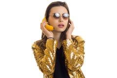 Νέα μοντέρνη γυναίκα στο χρυσό σακάκι με την μπανάνα Στοκ φωτογραφία με δικαίωμα ελεύθερης χρήσης