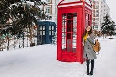 Νέα μοντέρνη χαμογελώντας γυναίκα κοντά στο κόκκινο τηλεφωνικό κιβώτιο στο χειμώνα Γοητευτικό κορίτσι στο γκρίζο παλτό, με το μακ στοκ εικόνες με δικαίωμα ελεύθερης χρήσης