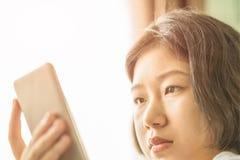 Νέα μουσική ακούσματος γυναικών από το κινητό τηλέφωνο Στοκ φωτογραφία με δικαίωμα ελεύθερης χρήσης