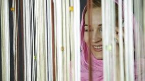 Νέα μουσουλμανική αραβική γυναίκα στο ρόδινο hijab που μιλά στο τηλέφωνο κυττάρων και που φαίνεται έξω το παράθυρο φιλμ μικρού μήκους